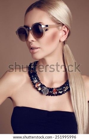 fashion studio photo of beautiful woman with long blond hair with bijou and sunglasses - stock photo