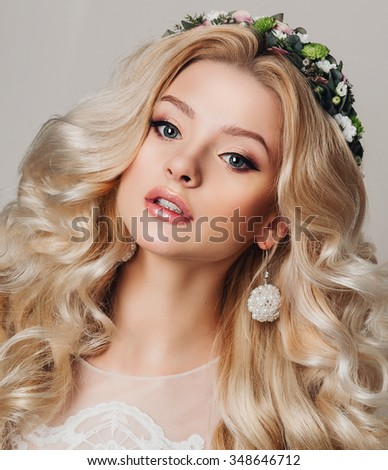 Fashion studio photo of beautiful young girl with long curly hairs. Jewelry. Hairstyle. Vogue style. Glamour Makeup. Fashionable blonde young woman posing, looking at camera. Studio shot. - stock photo