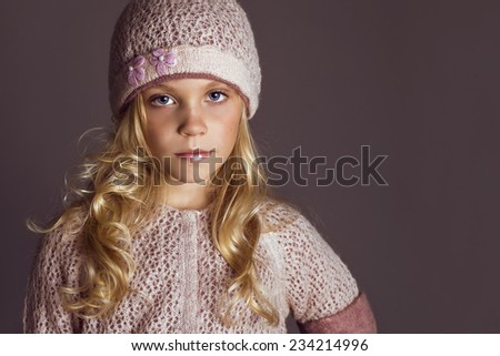 fashion studio photo of cute blond little girl  wearing purple sweater and knit hat