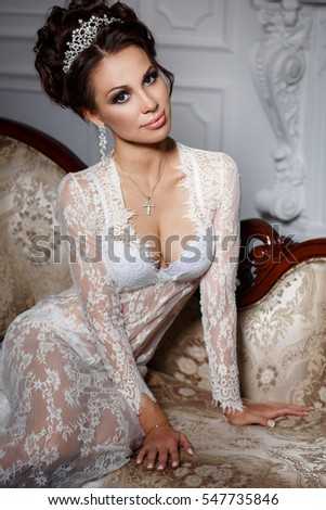 Fashion studio photo of gorgeous sexy woman in luxurious lace lingerie brunette hair in jewelry crown. Vogue style bride portrait in luxury bedroom interior. Bright makeup model with curly hairstyle