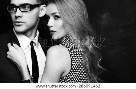 Fashion studio photo of office romance of sexy young couple of beautiful blond woman and handsome brunette businessman wearing in format suit,tie,glasses, Valentine's day