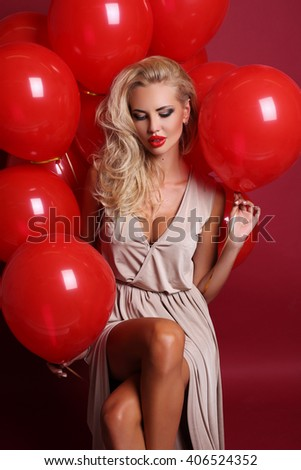 fashion studio photo of sexy beautiful woman with blond curly hair and bright makeup, wears elegant lingerie dress, posing with a lot of red air balloons - stock photo