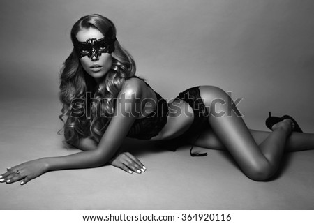 fashion studio photo of sexy gorgeous woman with long blond hair in black lingerie with lace mask on face - stock photo