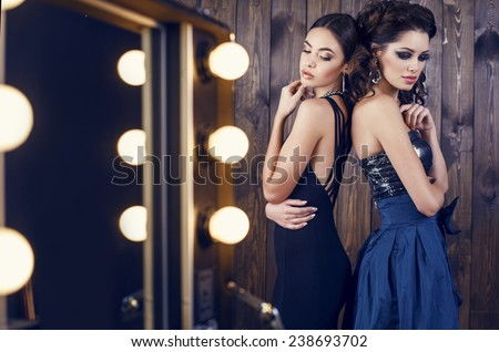 fashion studio photo of two beautiful sensual women with dark hair in luxurious dresses with bijou  - stock photo