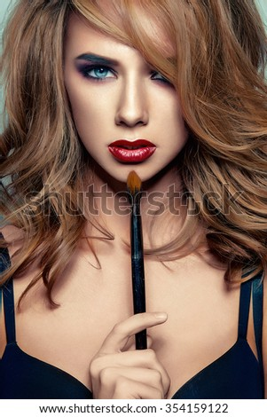 Fashion studio photo portrait of beautiful sensual girl with blond hair and bright makeup, holding makeup brush in hand. Beautiful face. Applying makeup. Retouched image. - stock photo