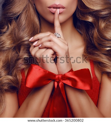 fashion studio portrait of beautiful girl with luxurious blond hair, with red lace bow on hands - stock photo