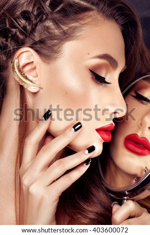 fashion studio portrait of beautiful glamour girl with perfect make up, with red lips looking at mirror