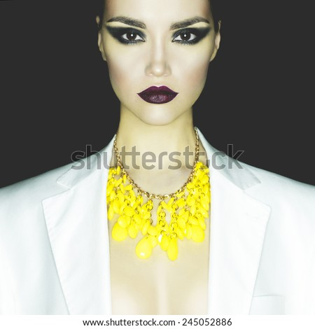 Fashion studio portrait of beautiful woman with necklace - stock photo