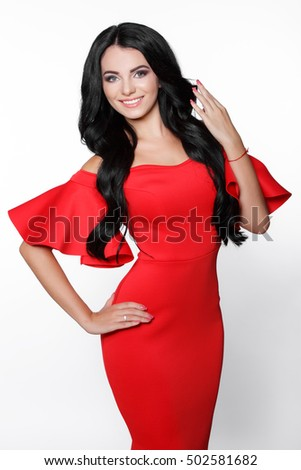 Fashion studio portrait of beautiful young woman in red dress. Glamour brunette girl with long curly hair and evening makeup. Smiling dark hair model in red dress with frill flounce isolated on white.