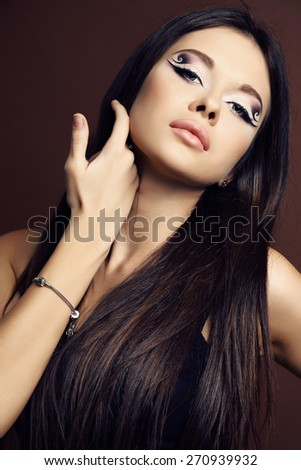 fashion studio portrait of beautiful young woman with dark  hair and bright extraordinary makeup
