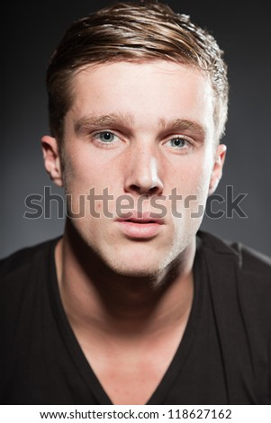 Fashion studio portrait of handsome young man with short brown hair.