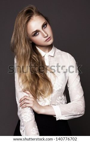 Fashion studio portrait of pretty model on dark grey background - stock photo