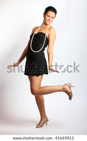 Fashion studio shot. Attractive young girl dancing with luxurious pearl necklage.