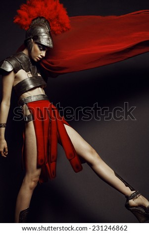 Fashion studio shot of beautiful woman in armor and in helmet with feathers on her head on black background