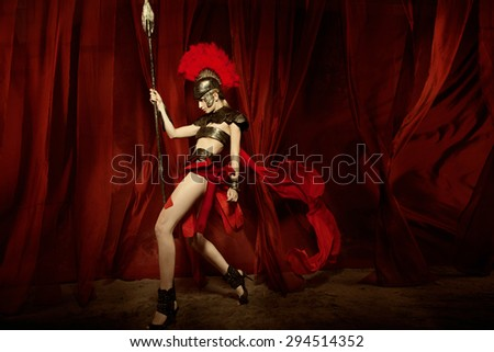 Fashion studio shot of beautiful woman in armour and helmet with feathers holding spear red curtain background