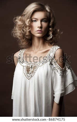 Fashion studio shot of beautiful woman with make-up and hairstyle wearing white evening dress - stock photo