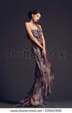Fashion studio shot of beautiful woman with makeup and hairstyle wearing evening dress - stock photo