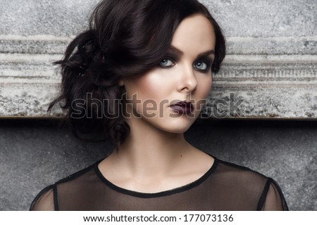 Fashion studio shot of beautiful young woman with stylish bright makeup and hairstyle