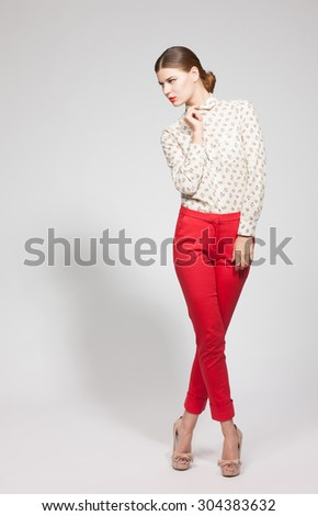 Fashion studio shot of model woman on high heels. Full-length portrait of serious young elegant woman in red trousers and white shirt. - stock photo