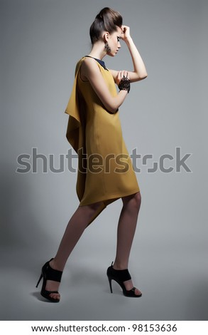 Fashion style - elegant brunette girl in trendy dress posing in studio. Series of photos - stock photo