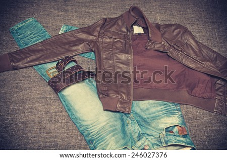Fashion style: leather jacket, blue jeans, a leather belt with a buckle. Youth urban clothing. Vintage style - stock photo