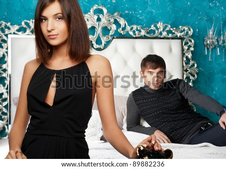 Fashion style photo of an attractive young couple inside luxury aristocratic interior of their apartment - stock photo