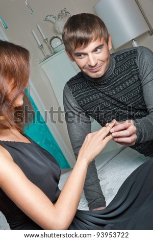 Fashion style photo of an attractive young couple inside luxury aristocratic interior of their apartment. Man making proposal to his girlfriend and giving a ring to her - stock photo