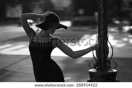 fashion style portrait of young trendy girl walking along the street at sunset. Concept of a little black dress. perfect body and silhouette on the  - stock photo