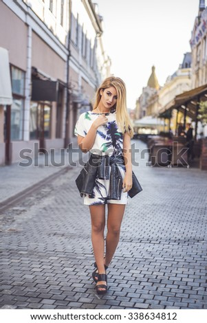 Fashion style shoot of young beautiful female model posing on european city street