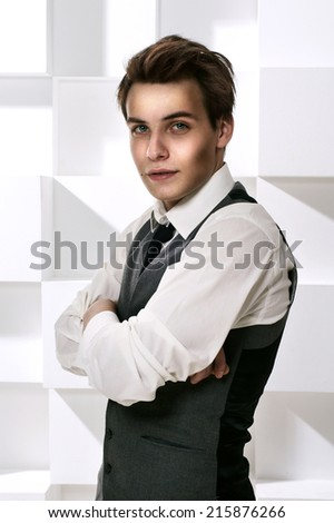 Fashion style studio portrait of young successful man dressed in stylish classic clothes with necktie with crossed arms and looking in camera - stock photo