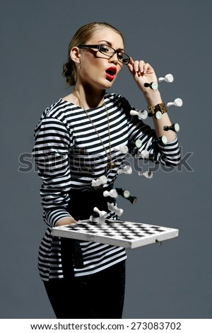 Fashion style vogue portrait of young pretty female model posing with chess. Flying figures - stock photo