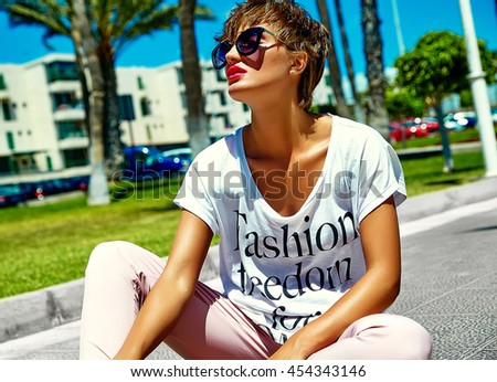 fashion stylish beautiful young brunette woman model in summer hipster bright colorful casual clothes posing on street background and sitting on asphalt - stock photo