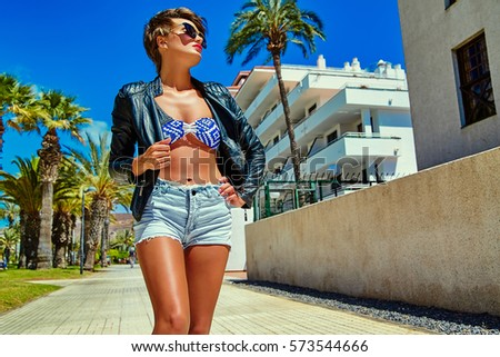 fashion stylish beautiful young brunette woman model in summer hipster casual leather jacket clothes posing on street background
