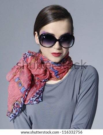 Fashion stylish girl in scarf on gray background - stock photo