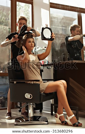 Fashion stylist hairdresser does a hairstyle to the client of a beautiful young girl in a fashionable salon. Hairdresser does hairstyle beautiful girl who looks in the mirror- stock photo.
