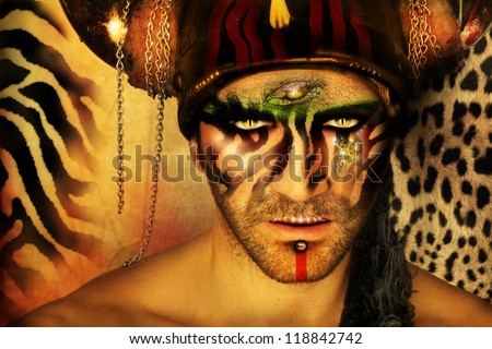 Fashion stylized concept portrait of a young man with tribal face painting and animal elements in front of a animal print background - stock photo