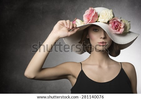 fashion summer close-up portrait of sexy brunette girl with black dress and big hat with colorful flowers, romantic spring style. she Looking in camera  - stock photo