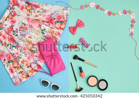 Fashion summer girl clothes accessories set. Woman essentials. Cosmetics, makeup. Stylish pink handbag clutch, trendy dress, necklace, sunglasses . Unusual overhead outfit, top view on blue - stock photo