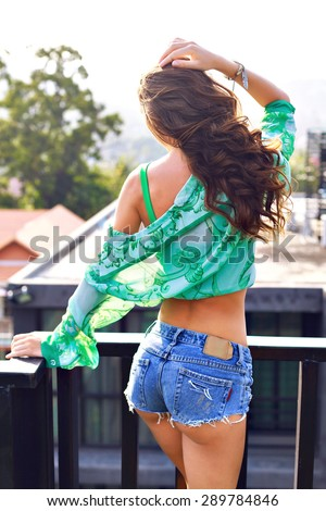 Fashion summer portrait of sexy woman with amazing fit body, wearing mini denim shorts, silk blouse and crop top, posing on balcony, urban glamour style, toned colors. - stock photo