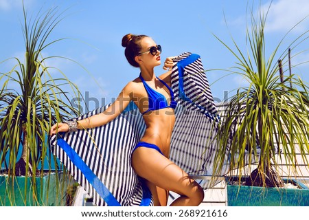 Fashion summer portrait of young sexy stunning woman with perfect slim fit body, relaxed on luxury vacation. wearing stylish bright bikini make up and sunglasses. - stock photo