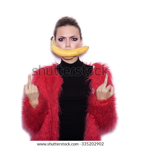 Fashion swag female model wearing black dress and pink fur coat making fun with banana. Cute girl having fun over white background not isolated - stock photo