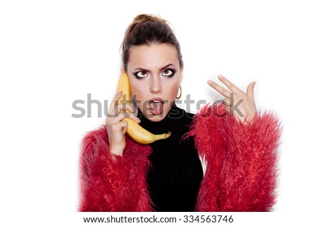 Fashion swag female model wearing black dress and pink fur coat making fun with banana. Woman holding a banana as a telephone over a white background not isolated - stock photo
