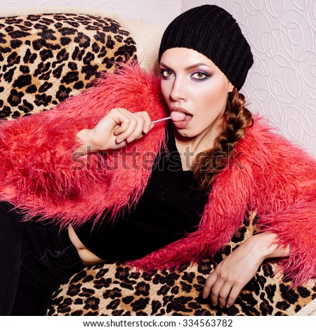 Fashion swag Girl wearing black dress and beanie and pink fur coat licking candy. Freak young sexy Woman lying on leopard sofa. Vogue style indoors shot  - stock photo