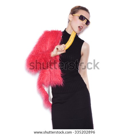 Fashion swag woman wearing black dress and pink fur coat making fun with banana. Cute girl having fun over white background not isolated - stock photo