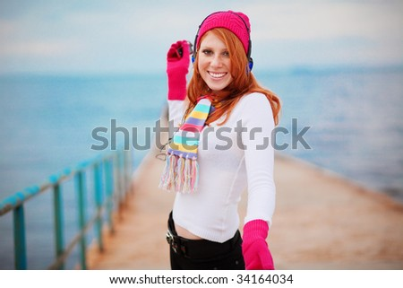 Fashion teenage girl wearing winter clothing is listening to music near the sea - stock photo
