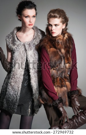 Fashion two girl wearing modern dress posing in the studio - stock photo
