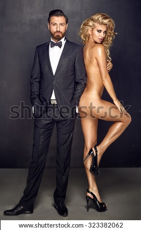 Fashion type portrait of an elegant man and naked woman - stock photo