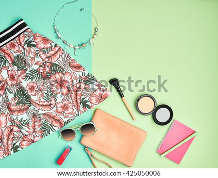 Fashion urban summer outfit, girl clothes set, cosmetics, makeup accessories. Stylish handbag clutch, trendy pink dress, necklace, sunglasses. Woman essentials. Unusual overhead, top view on blue - stock photo