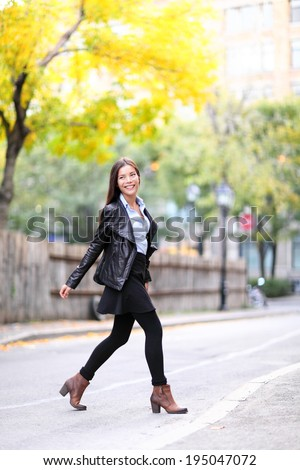 Fashion urban young woman living city lifestyle walking in leather jacket crossing streets in full length in autumn fall. Trendy modern female. Multiracial Asian Caucasian model. - stock photo
