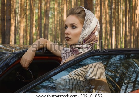 Fashion vintage woman standing near vehicle with opened door - stock photo